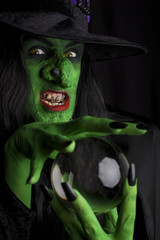 Evil witch and her crystal ball, black background.