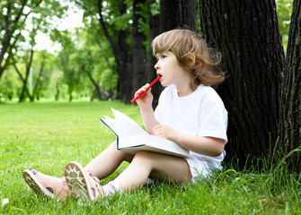 Portrait of little girl reading a book in the park