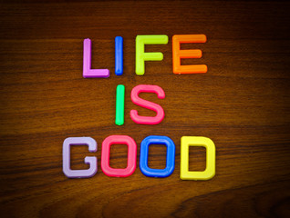Life is good in colorful toy letters on wood background
