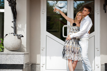 Young man embracing smiling girlfriend near door into new house