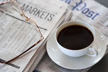 Hot coffee and newspaper. reading glasses