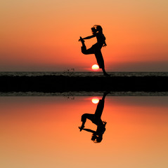 silhouette of female dancer in sunset at beach with reflection