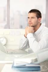 Daydreaming businessman sitting at desk