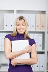 lächelnde frau im büro trägt ihren laptop