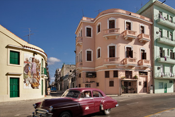 Red car and pastel-colored houses in Havana