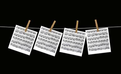 Spartiti musicali appesi su fondo nero