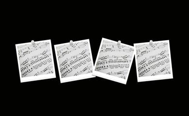 Spartiti musicali appesi con puntine da disegno su fondo nero