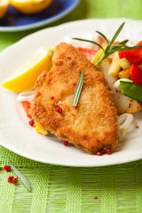 Breaded fish fillet with pan-fried vegetables