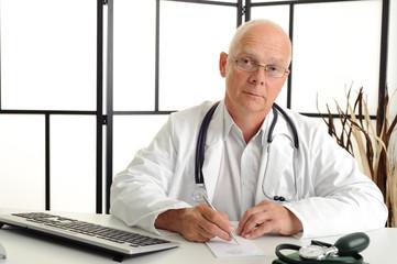 Älterer Arzt schreibt ein Rezept und schaut in die Kamera
