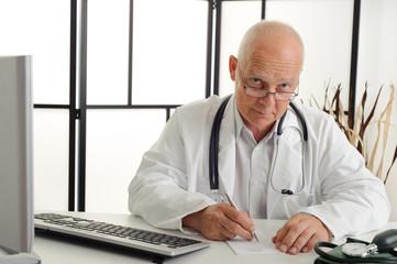 Älterer Arzt am Schreibtisch blickt über Brille