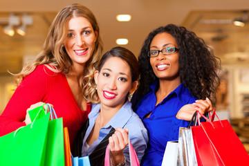 Frauen shoppen in Einkaufszentrum mit Weihnachtsschmuck