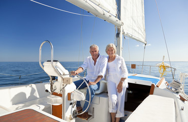 Happy Senior Couple At The Wheel of a Sail Boat