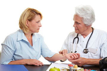 Ärztin misst Blutdruck mit Fingern