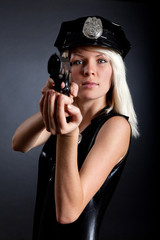 Beautiful sexy police girl with handgun and handcuffs