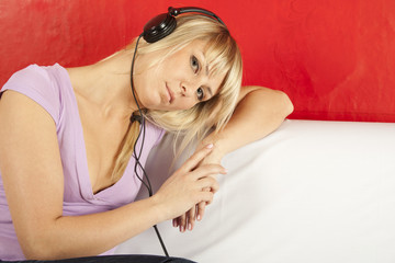 Attractive young woman on a sofa with headphones