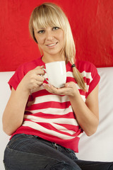 Young woman sitting on a sofa drinking coffee