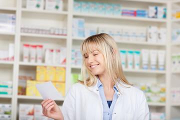 lächelnde apothekerin mit rezept