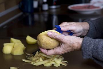 Frau schält Kartoffeln