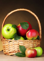 Basket of organic apples on brown background