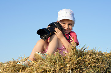 Little girl sitting on straw with a camera