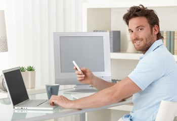 Man using computer and phone at home