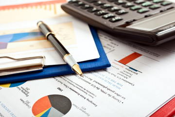 Pen on financial documents and calculator