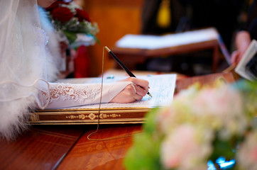 bride signs a document