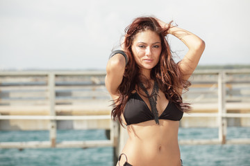 Woman in a bikini with hands in hair