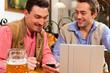 Zwei Freunde in bayerischer Wirtschaft mit Laptop