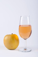 A glass filled with orange substance and an apple