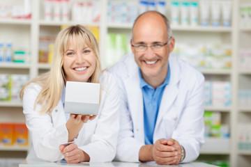 zwei kollegen in der apotheke zeigen ein medikament