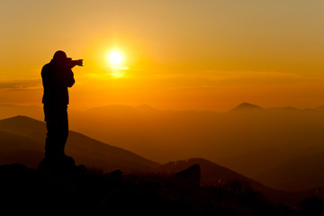 photographer taking picture of landscape during sunset