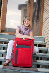 Happy woman with luggage on her home stages