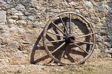 old wheel at a brickwall