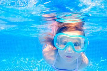 blond child girl underwater swimming in pool