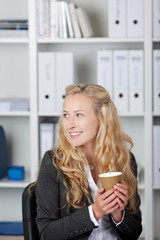 lächelnde frau mit kaffee im büro