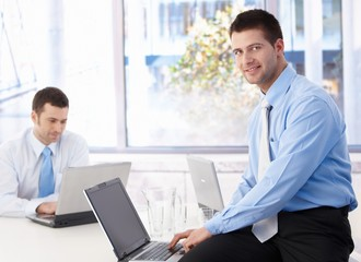 Young businessman using laptop smiling in office