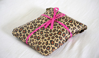 present wrapped in leopard print with pink ribbon