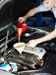 Motor mechanic topping up oil of a car in a garage