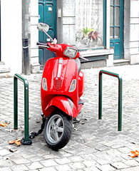 red scooter parked on sidewalk