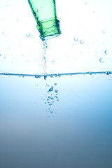 Green bottle and water splashing