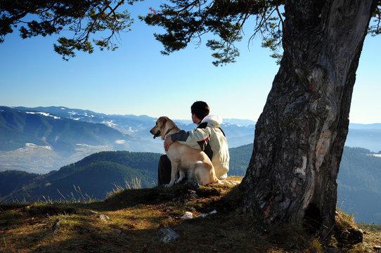 Young man enjoying mountain view with his dog