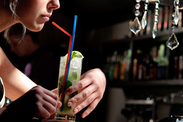 A young blond girl drinking coctail mohito with a straw in a caf