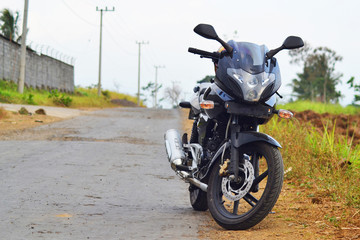 black motorcycle beside the road in a village