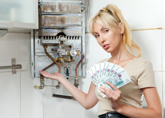 housewife counts up money for repair of a gas water heater..