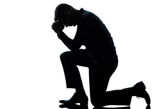 silhouette man kneeling sadness praying full length