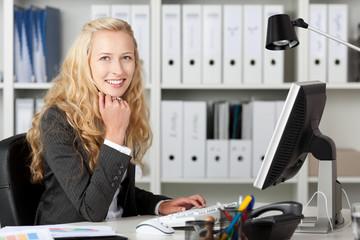 lächelnde blonde frau am computer