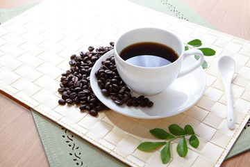Coffee bean and hot coffee with green leaf
