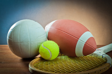 Assorted sports equipment.Tennis and racket,rugby and volleyball