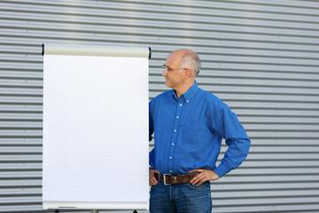 mann steht neben weißem flipchart